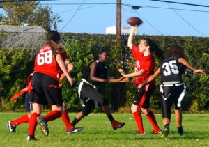 OVERHEAD: Quarterback Nicole Feder evades a sack as she quickly throws the ball Sept. 22 against the LA Adventist Eagles