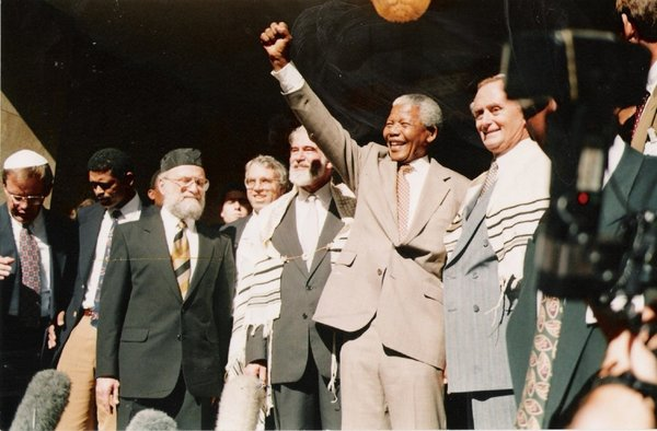 Nelson Mandela saluted the crowd at the Green and Sea Point Hebrew Congregation in Cape Town in 1994, joined by (from left) Rabbi Jack Steinhorn; Israel's ambassador to South Africa, Alon Liel; Chief Rabbi Cyril Harris; and Mervyn Smith, chairman of the South African Jewish Board of Deputies;