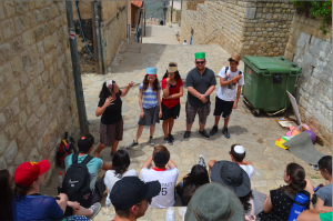 ALLEYS: Seniors listen to a guide during their tour of Tzfat May 26. They have sometimes gathered for informal davening outdoors.