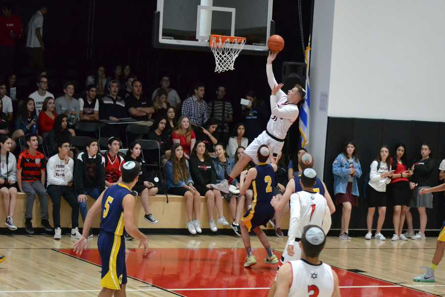 EFFORT: Shalhevet's Sammy Ellenhorn leaps over TABC defense in Game 4 Nov. 10. The Firehawks won, 44-42.