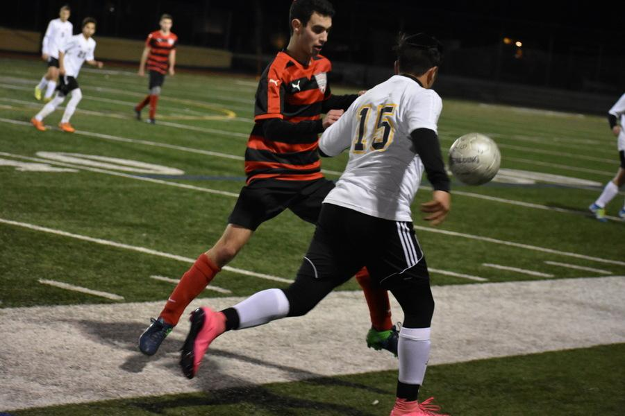 SCRAMBLE: Firehawk junior Isaac Kahtan fights YULA No. 15 for the ball at rivalry game in Encino Jan. 14.