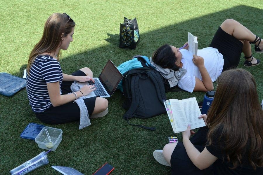 Concentration%3A+Three+seniors+do+their+homework+up+on+the+turf.+